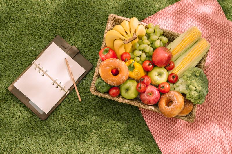 Summertime picnic setting on the grass with open picnic basket, fruit, salad and cherry pie stock photography