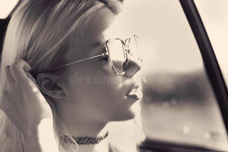 Summertime sadness girl. Girl in a car feel summertime sadness wearing sunglasses fashion royalty free stock images