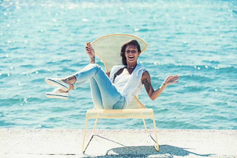 Summertime of woman eating ice cream at cafe. happy woman relax at sea resort. Summer holidays and travel vacation. Smiling girl enjoying sun on chair at sea royalty free stock images