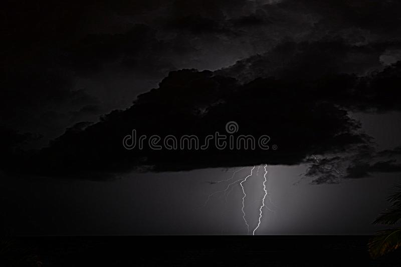 Lightning on the ocean horizon show us the raw power of mother nature. Summertime storms are dramatic displays of nature with thunder and lightning combined with royalty free stock image