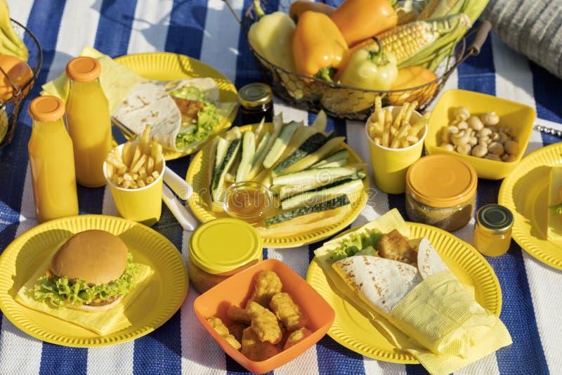 summertime Un picnic sulla spiaggia Hamburger e pite, verdure fotografia stock libera da diritti