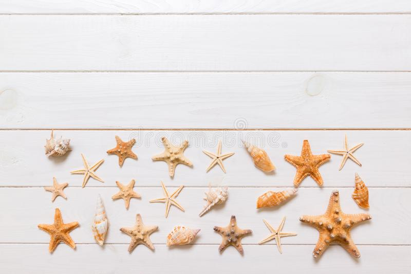 Summertime wooden table with starfish and seashells on a white background top view. Copy space background, summer concept royalty free stock images