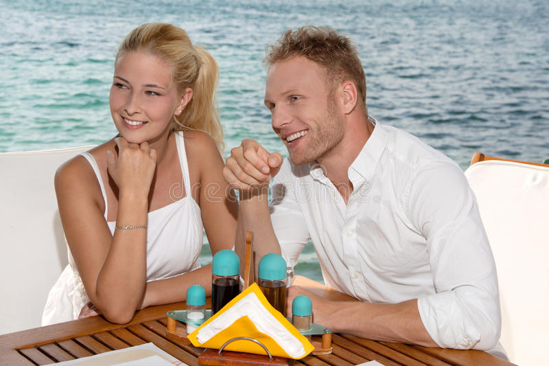 Summertime: young couple sitting in a restaurant next to the sea. Young couple sitting at restaurant next to the sea stock images
