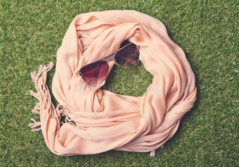 Summery pastelowi okulary przeciwsłoneczni na trawie i szalik zdjęcie royalty free