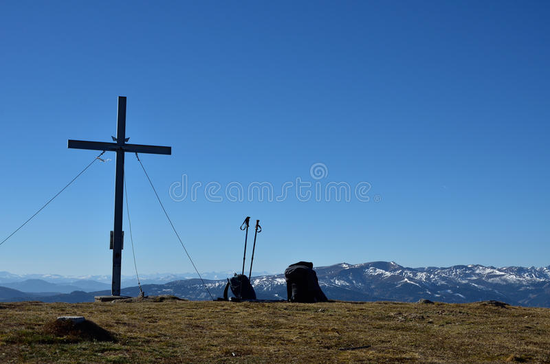 Summit cross with backpacks next to it stock photography