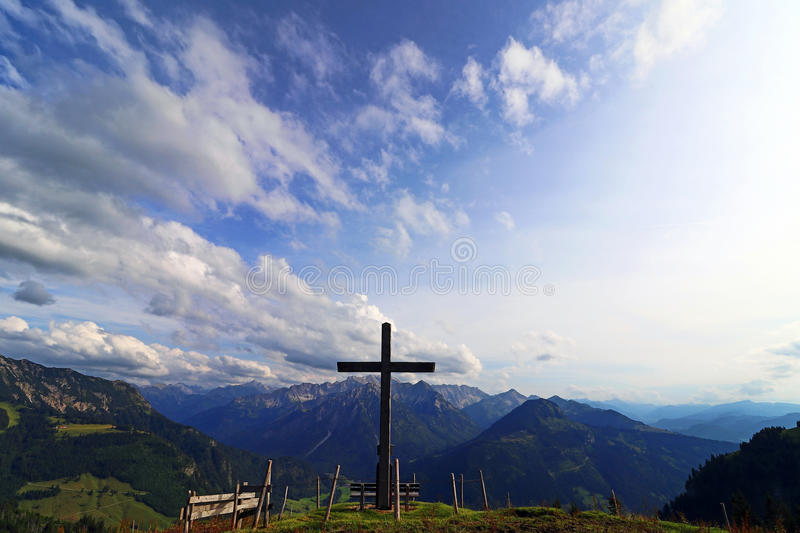 A summit cross in the evening light against the sky. A summit cross in the Alps. A summit cross in the Allgäu Alps. A summit cross in the evening light stock photo