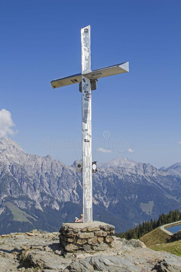 Summit cross of the Hohe Asitz. The summit of the Hohe Asitz in the ski and hiking area Leogang and Saalfelden allows an impressive panoramic view of the royalty free stock image