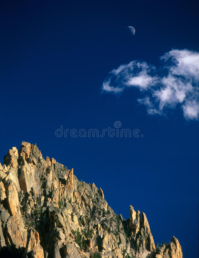The summit of The Grand Mogul and rising moon, Sawtooth Wilderness, Sawtooth National Recreation Area, Idaho royalty free stock image
