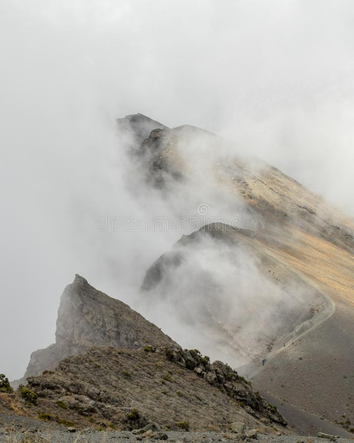 Trekking Mount Meru, Arusha National Park,. The summit of Mount Meru partly covered by clouds, Arusha National Park, Tanzania royalty free stock image