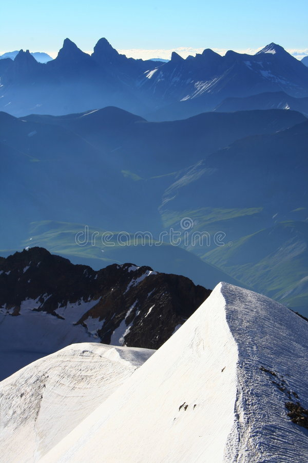 Summit and ridge with snow. Ridge with snow atop of the mountain with an impressive point of view stock photo