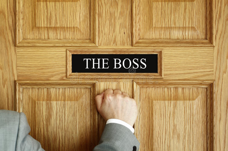 Summoned to see The Boss. Businessman knocking on a door to The Boss office concept for meeting, trouble, problems, promotion or being fired royalty free stock image