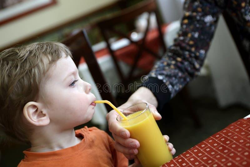 Sumo de laranja bebendo da criança imagem de stock royalty free