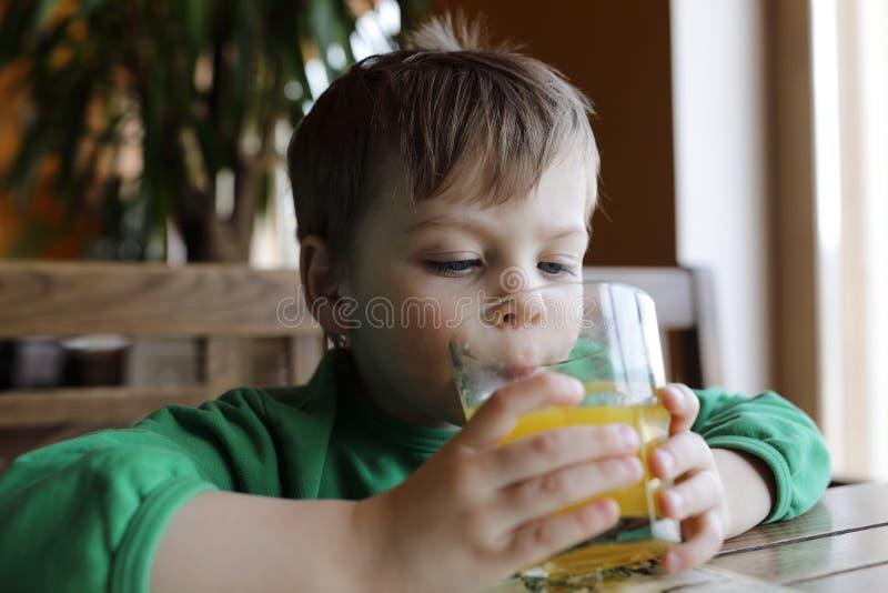 Sumo de laranja bebendo do menino fotos de stock