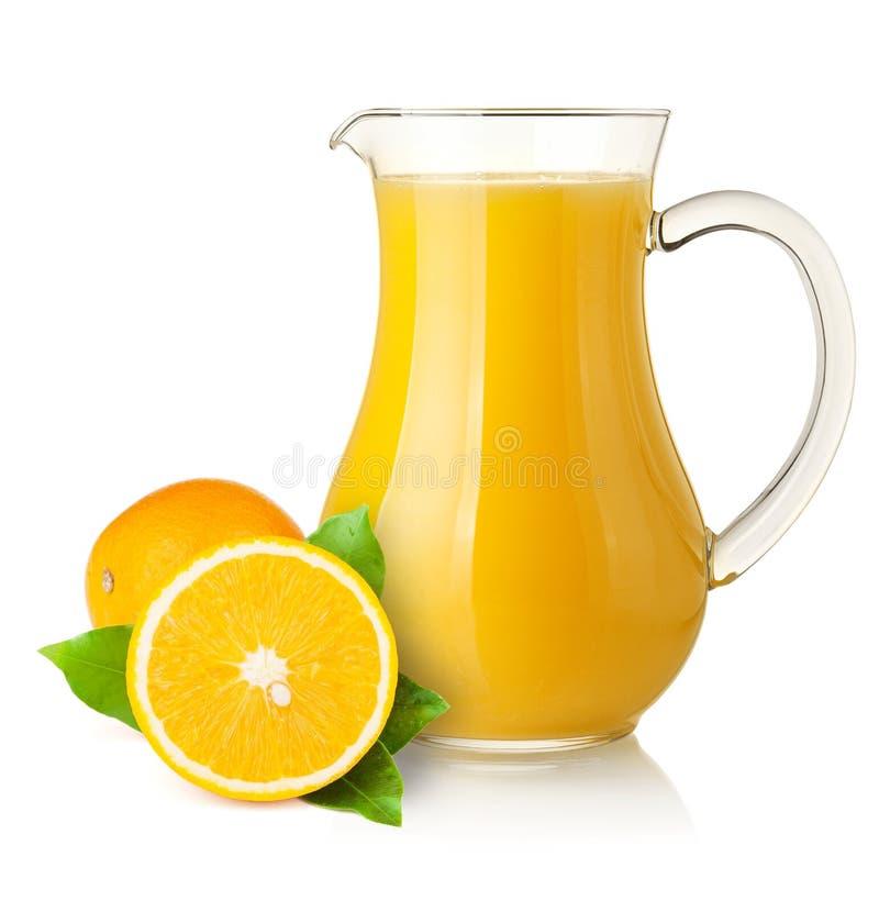 Sumo de laranja no jarro e nas laranjas imagens de stock