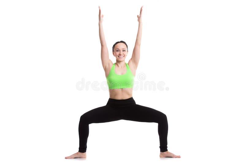 Sumo wrestler yoga pose. Slender fitness girl doing sumo squat exercises on white background, Goddess Pose (Utkata Konasana), Temple or sumo wrestler pose royalty free stock images