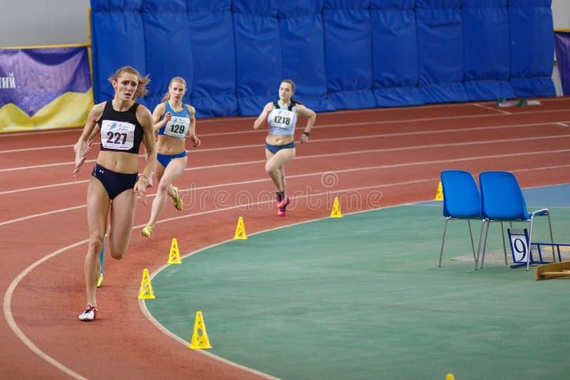 SUMY, UCRANIA - 17 DE FEBRERO DE 2017: las deportistas compiten en el ` s los 400m de las mujeres que corren en un evento interio imagen de archivo