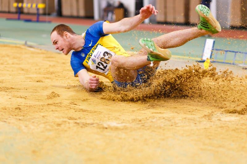 SUMY, UCRANIA - 17 DE FEBRERO DE 2017: Serhiy Nykyforov que realiza su salto de longitud en la calificación en pista interior ucr imagenes de archivo
