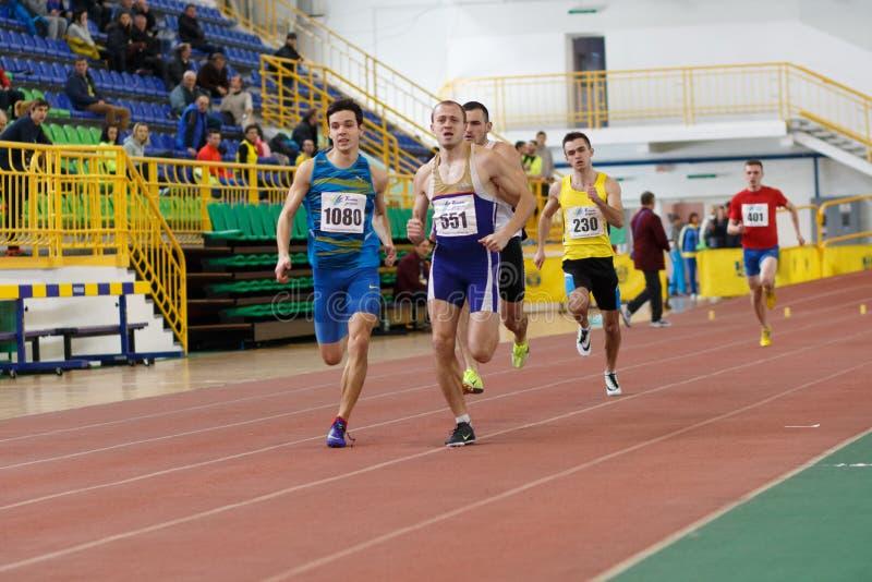 SUMY UKRAINA, LUTY, - 17, 2017: sportowowie biega kwalifikację ścigają się w mężczyzna ` s 400m biega w salowym śladzie i fotografia royalty free