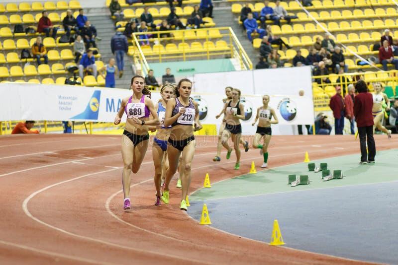 SUMY, UKRAINE - FEBRUARY 17, 2017: Mariya Shatalova 212 and Olena Sokur 889 with other sportswomen running in final. Of 3000m race on Ukrainian indoor track and stock image
