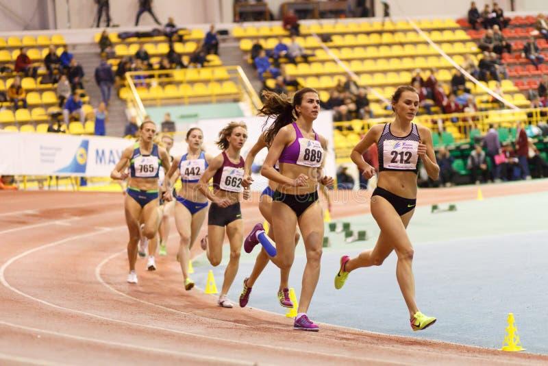 SUMY, UKRAINE - FEBRUARY 17, 2017: Mariya Shatalova 212 and Olena Sokur 889 with other sportswomen running in final. Of 3000m race on Ukrainian indoor track and royalty free stock photo