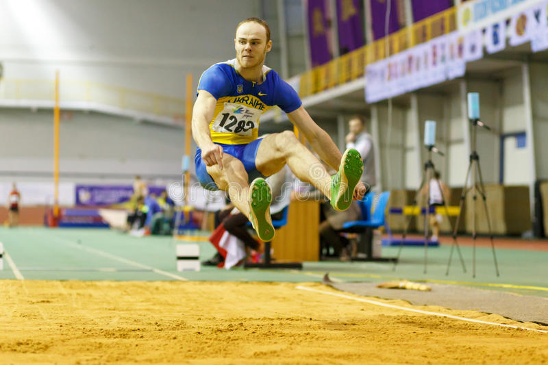 SUMY, UKRAINE - FEBRUARY 18, 2017: Serhiy Nykyforov performing his long jump in final on Ukrainian indoor track and royalty free stock photo