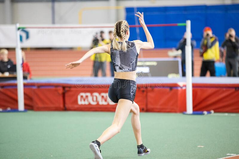 SUMY, UKRAINE - FEBRUARY 22, 2020: Yaroslava Mahuchikh champion in high jump speed up in her attempt at Ukrainian indoor. Track and field championship 2020 stock photography