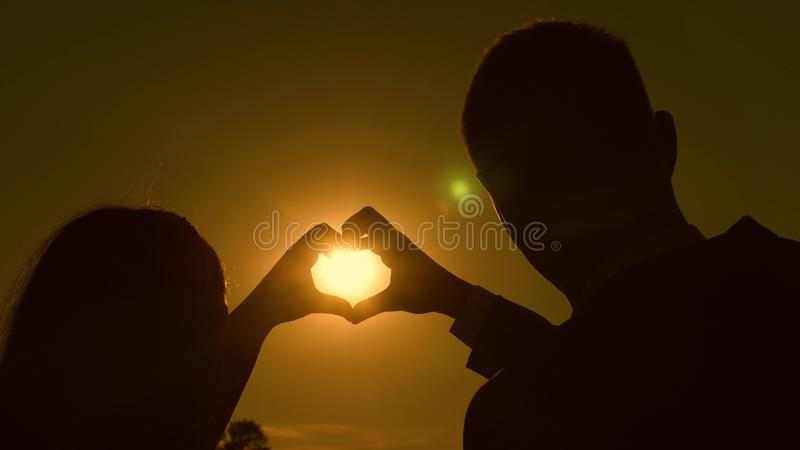 Sun à disposicão Trabalhos de equipe de um par de amor o par no amor mostra o símbolo do coração com mãos Noivos que fazem um cor imagens de stock royalty free