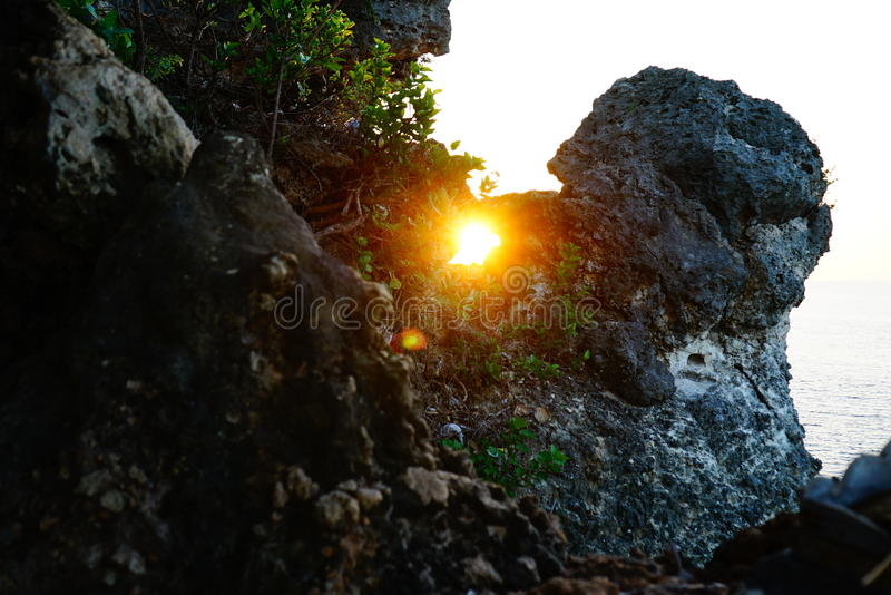 Sun à l'intérieur de roche par la mer photographie stock