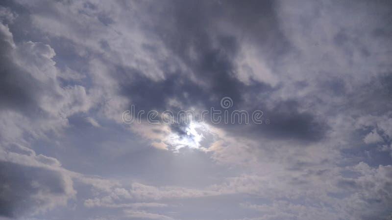 The Sun é atrás das nuvens mas ainda do brilho imagem de stock