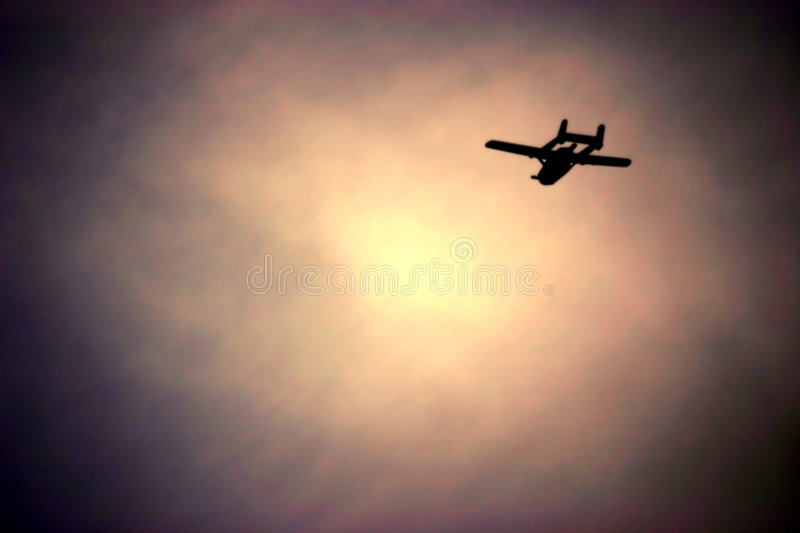 Into the Sun. Airplane flying into the sunset royalty free stock images