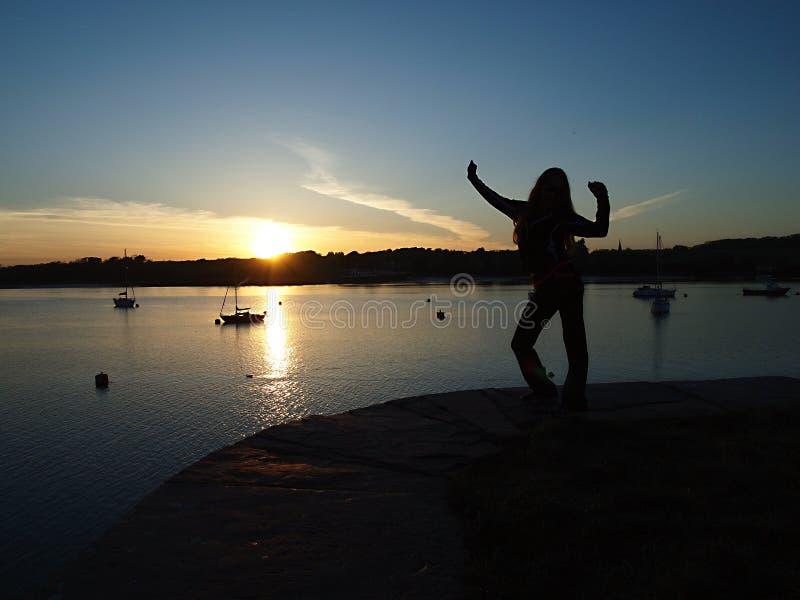 Sun ajustou-se sobre o lago, botes está no fundo fotografia de stock royalty free