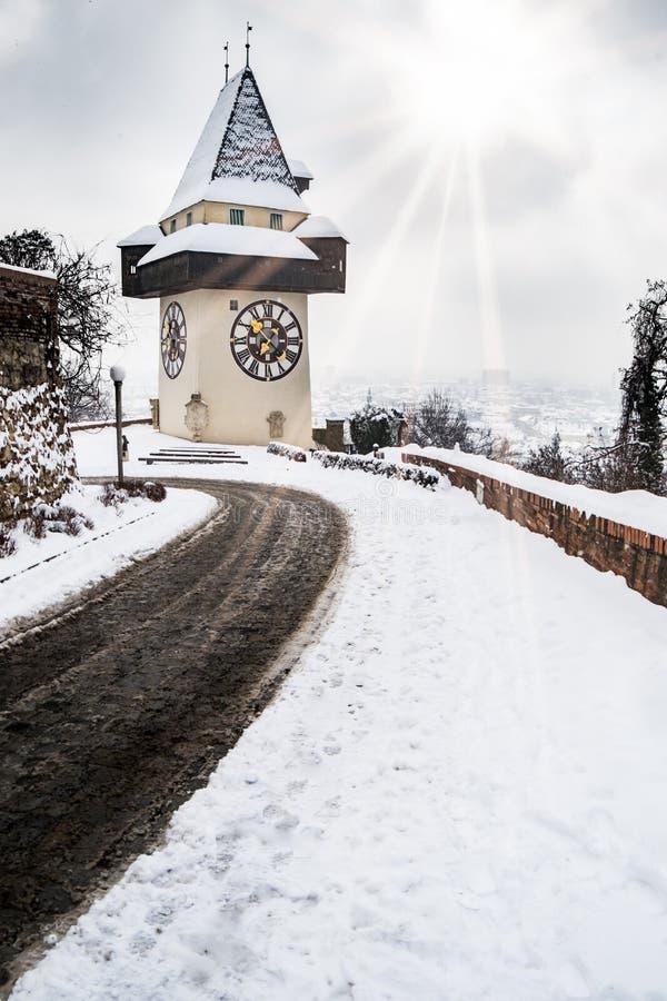 Sun alarga-se sobre o marco coberto de neve do clocktower de Uhrturm de Graz foto de stock
