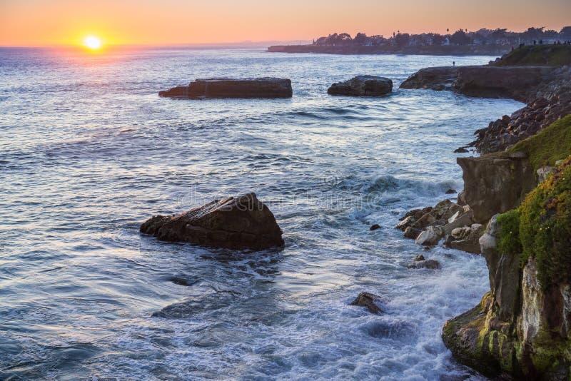 Sun alrededor a fijar; la costa costa rugosa del Océano Pacífico en el primero plano; Santa Cruz, California fotos de archivo