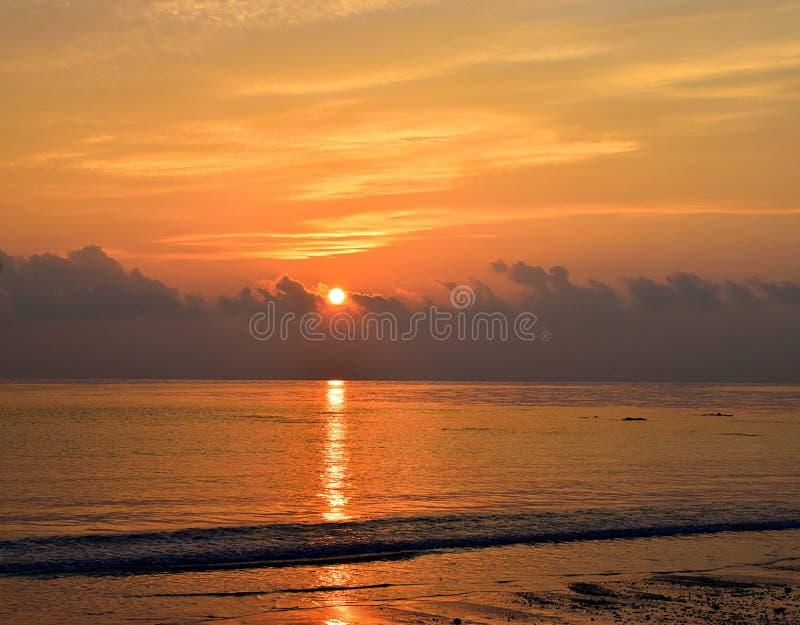 Sun amarillo brillante brillante que sube en el horizonte sobre el océano con la reflexión de oro en agua y colores calientes ama imagen de archivo libre de regalías