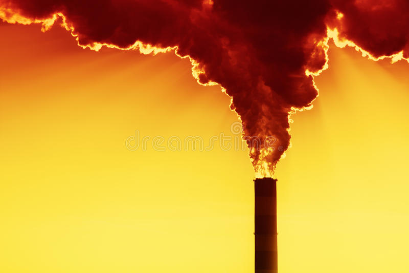 Sun atrás do fumo da fábrica foto de stock royalty free