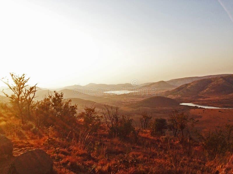 Sun au-dessus de dirt_South rouge Afrique du ` s de l'Afrique photographie stock