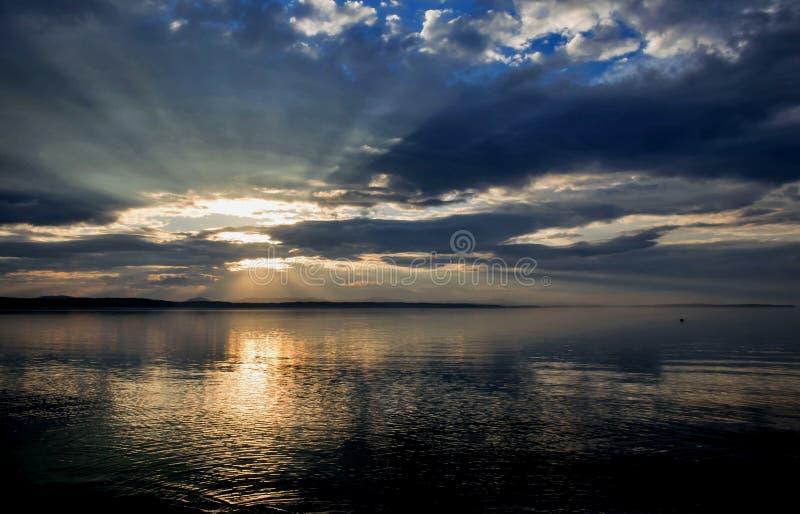 Sun au-dessus du lac brille par les nuages gris photographie stock