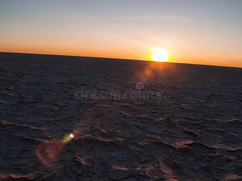 Sun auf gebogenem Horizont über gebackener, trockener gebrochener Kruste von Makgadikg lizenzfreies stockbild