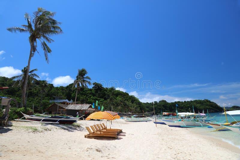 Sun-Aufenthaltsräume mit Regenschirmen bei Ilig Iligan setzen, Boracay-Insel, Philippinen auf den Strand lizenzfreies stockfoto