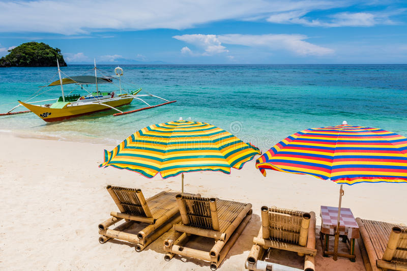 Sun-Aufenthaltsräume mit Regenschirmen bei Ilig Iligan setzen, Boracay-Insel, Philippinen auf den Strand stockbild