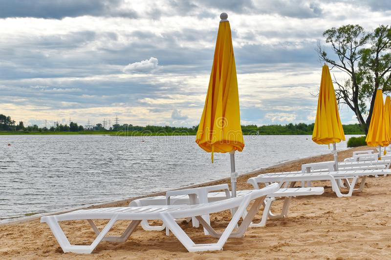Sun beds on the beach with yellow umbrellas in  summer royalty free stock photo