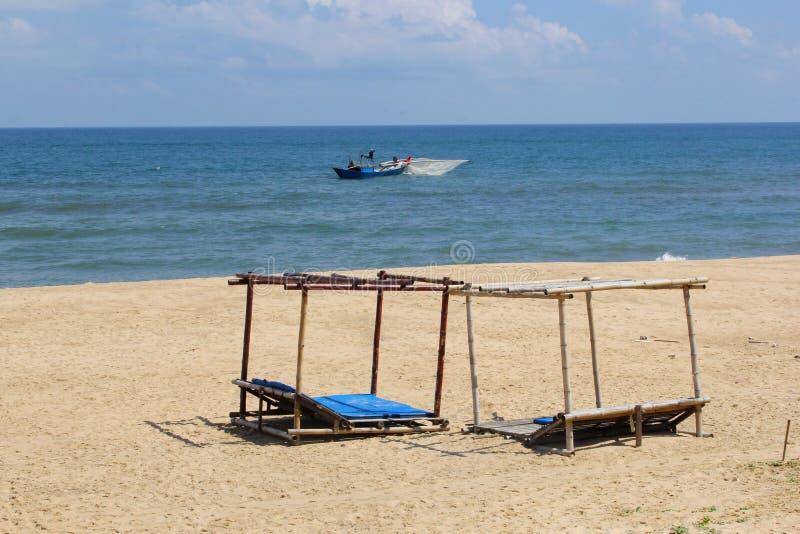 Beach sun beds blue ocean fishing boat, Hoi, Vietnam royalty free stock photography