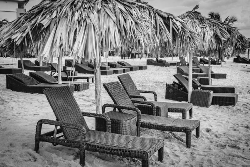 Sun beds/ lounge chairs and straw thatch roof umbrellas on tropical beach. Empty Sun beds/ lounge chairs and straw thatch roof umbrellas on white sand tropical stock photo