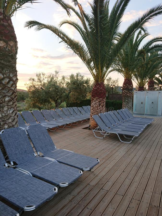 Sun beds under palm trees in Greece royalty free stock image