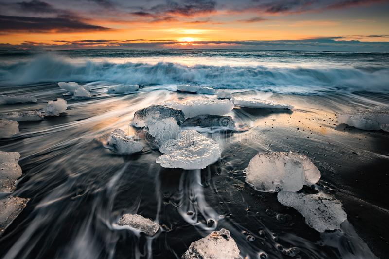 Sun begins to rise over ice chunks at Ice beach at Jokulsarlon. Iceland stock photo