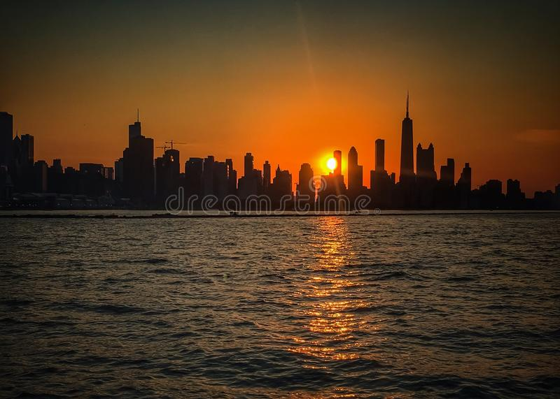 Skyline of Chicago seen from boat on Lake Michigan. Sun begins to set behind the iconic skyline of the great City of Chicago, and reflecting off of the waters of royalty free stock photos