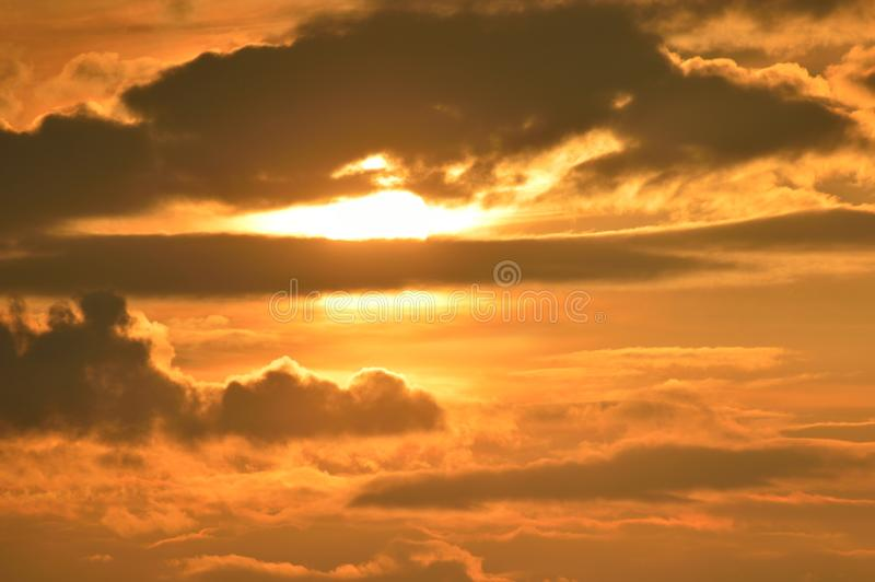 Sun behind a cloud. The evening sun shone behind a cloud. In that way, some recent hot rays stray over the earth royalty free stock image