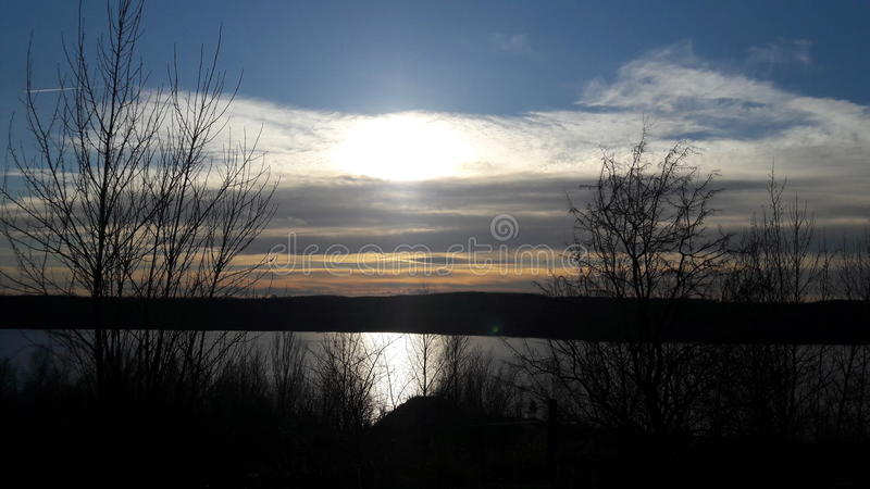 Sun behind clouds above lake royalty free stock photo