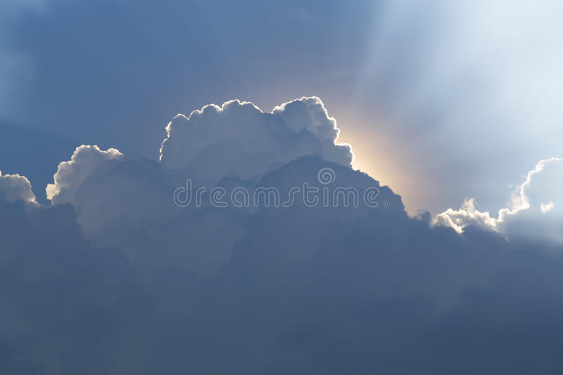 Sun behind clouds creating god rays. Clear sky on the top and storm clouds on the bottom. Sun is behind the clouds forming white god rays stock image