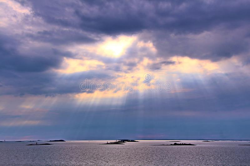 The sun behind the clouds with rays of light shining down on sea. Sky background. Photo in artistic style royalty free stock images